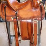 Rancher - 2 strand barbed wire w channels, stirrup lthrs out, 2 in bell stirrups, latigo wrap, straight-back, floral conchos