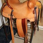 Rancher -2 strand sswirl w channels, corner basket wv, 2-tone, stirrup leathers out, corner basket weave, latigo wrap, 2 in stirrups, floral conchos, straight-back