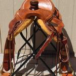 Rancher - basket weave border, 4 oak leaves, cheyenne roll, latigo, 3 in bell stirrups, saddlebags, floral conchos, stirrup lthrs out (2)