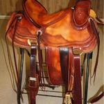 Rancher - dark straight-back, stirrup leathers out and dar, 2-tone, latigo, 2 in bell stirrups, corner bskt wv, barbed wire w rope and scallop border, floral