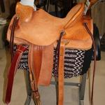 Wade -rough-out seat,fenders,and skirts,straight-back cantle,mule hide wrap,stirrup leathers out and tooled,rawhide oxbows,corner Santa Fe Diamond,s-swirl w channels,floral conchos