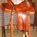 Wade - brand on fenders and jockey, straight-back, mule hide, bucking rolls, oxbows, barbed wire w scallop border, star conchos, rawhide front