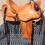 Wade - Santa Fe and s-swirl, corner basket weave, mule hide, bucking rolls, floral conchos, cheyenne roll, stirrup lthrs out, cinch keeper on side string, brass oxbows (1)